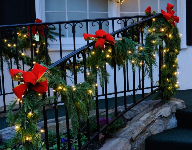 Lighted Christmas garland porch decorations with red bows/