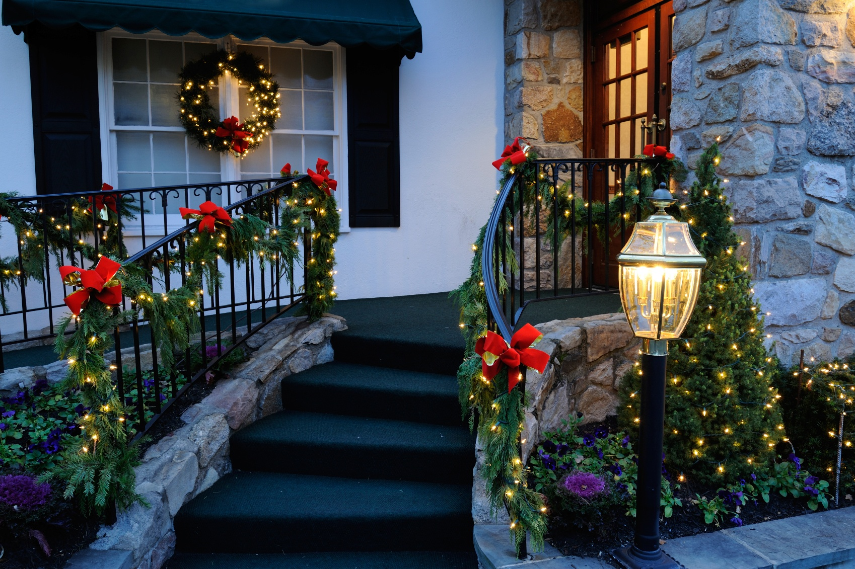 Lighted garland and red bows create a classic Christmas porch!