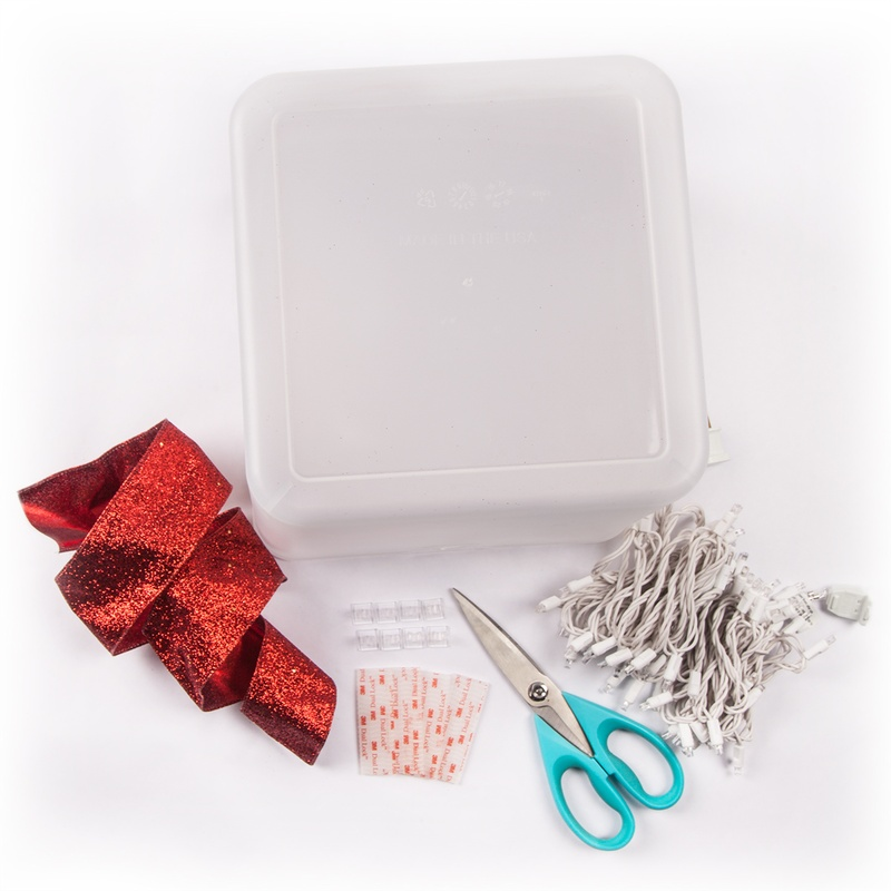 Create a DIY lighted gift box decoration for Christmas using a plastic container, ribbon and string lights!