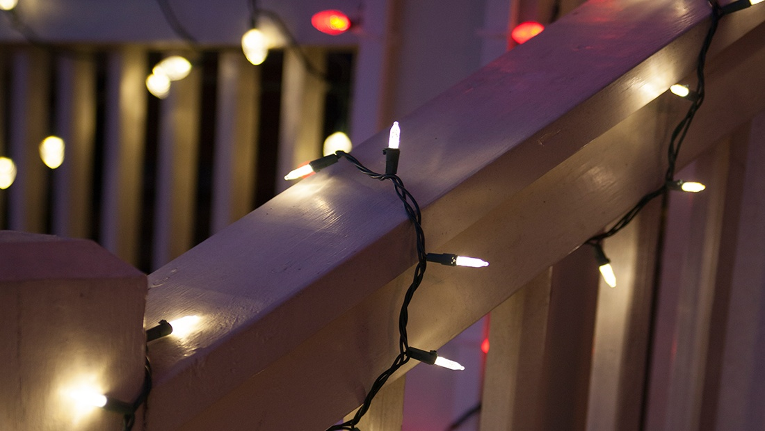 Wrap porch railings with mini Christmas string lights.
