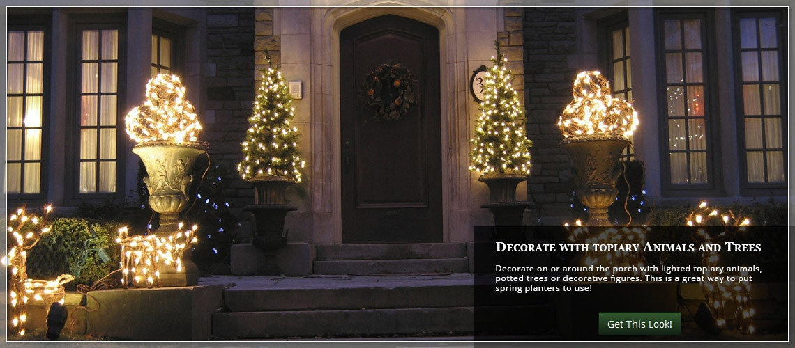 flank each side of the door with lighted topiary animals and potted trees