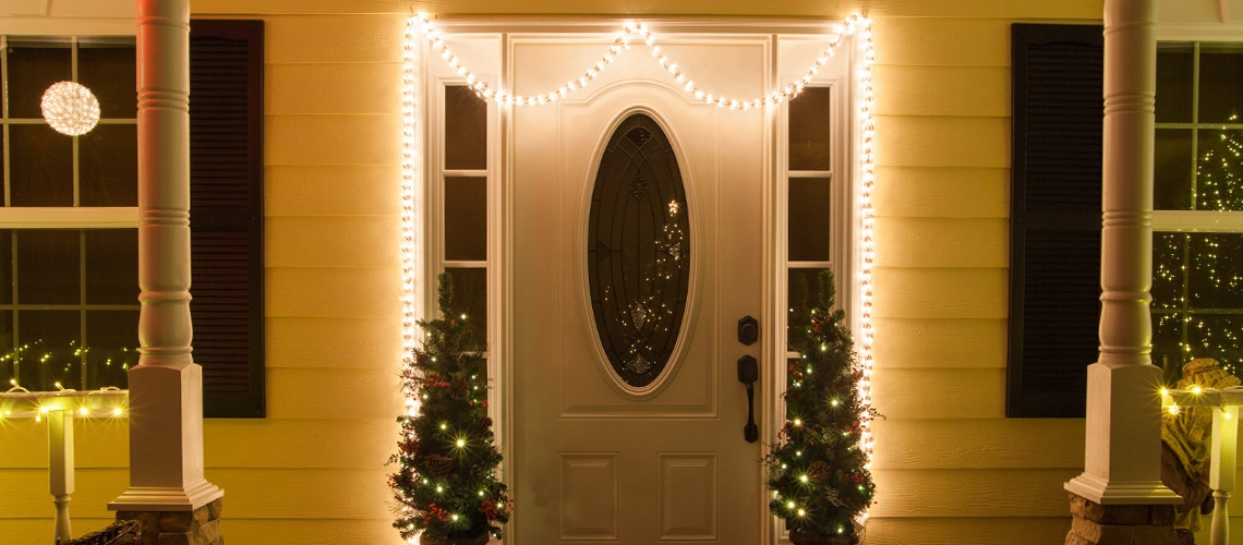Christmas garland lights frame a front door