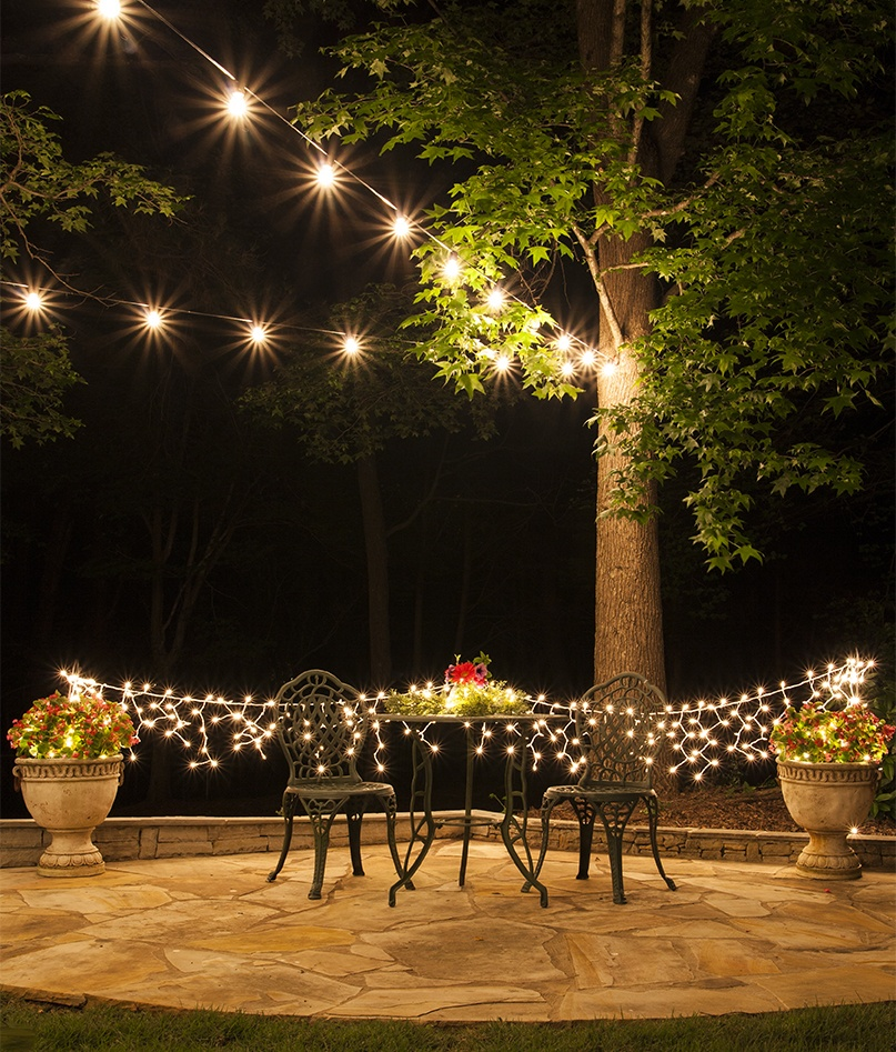 Outdoor living area with patio lights and icicle string lights. Beautiful outdoor dinner party ideas!