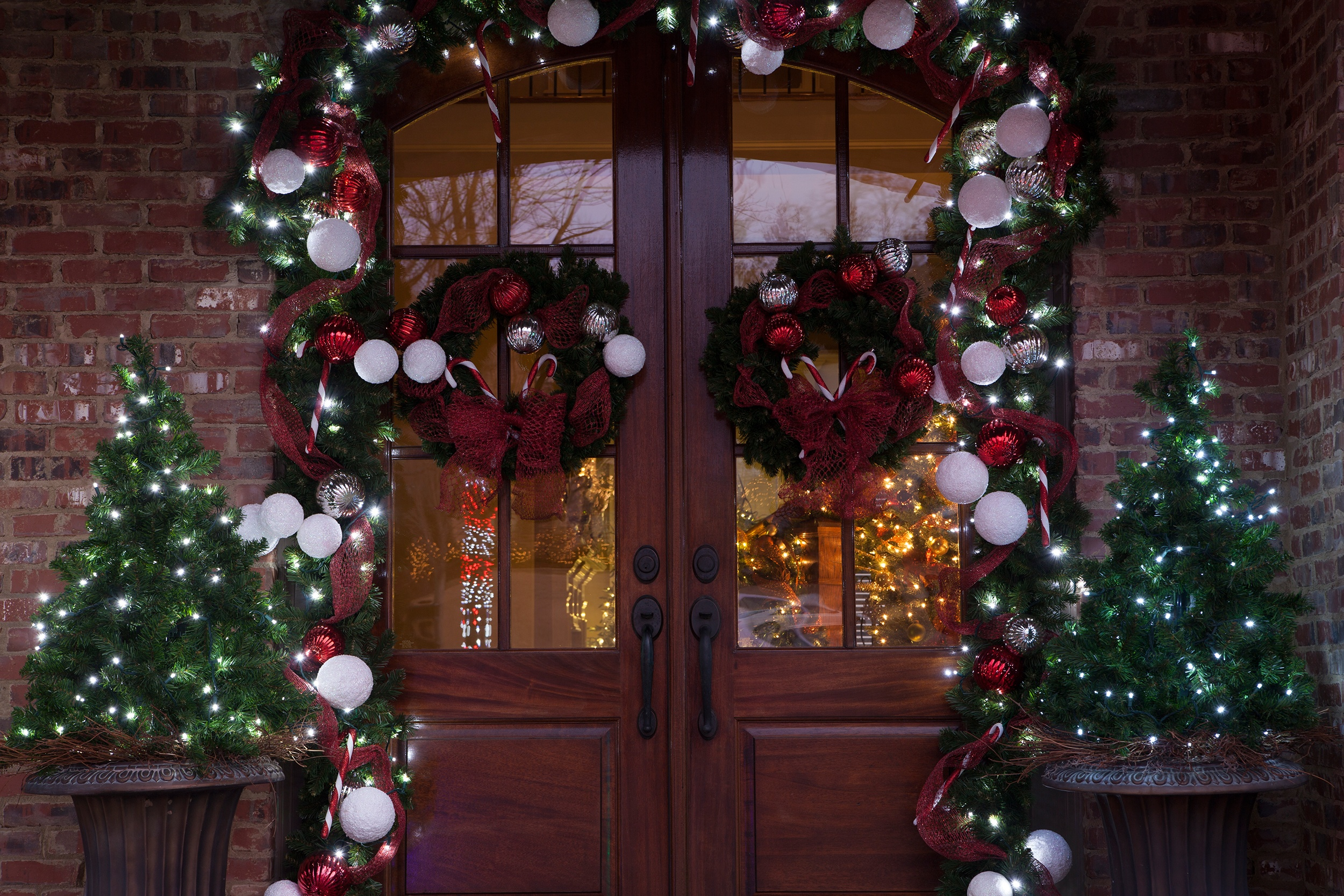 decorate with christmas garland wreaths and trees on and around the front door