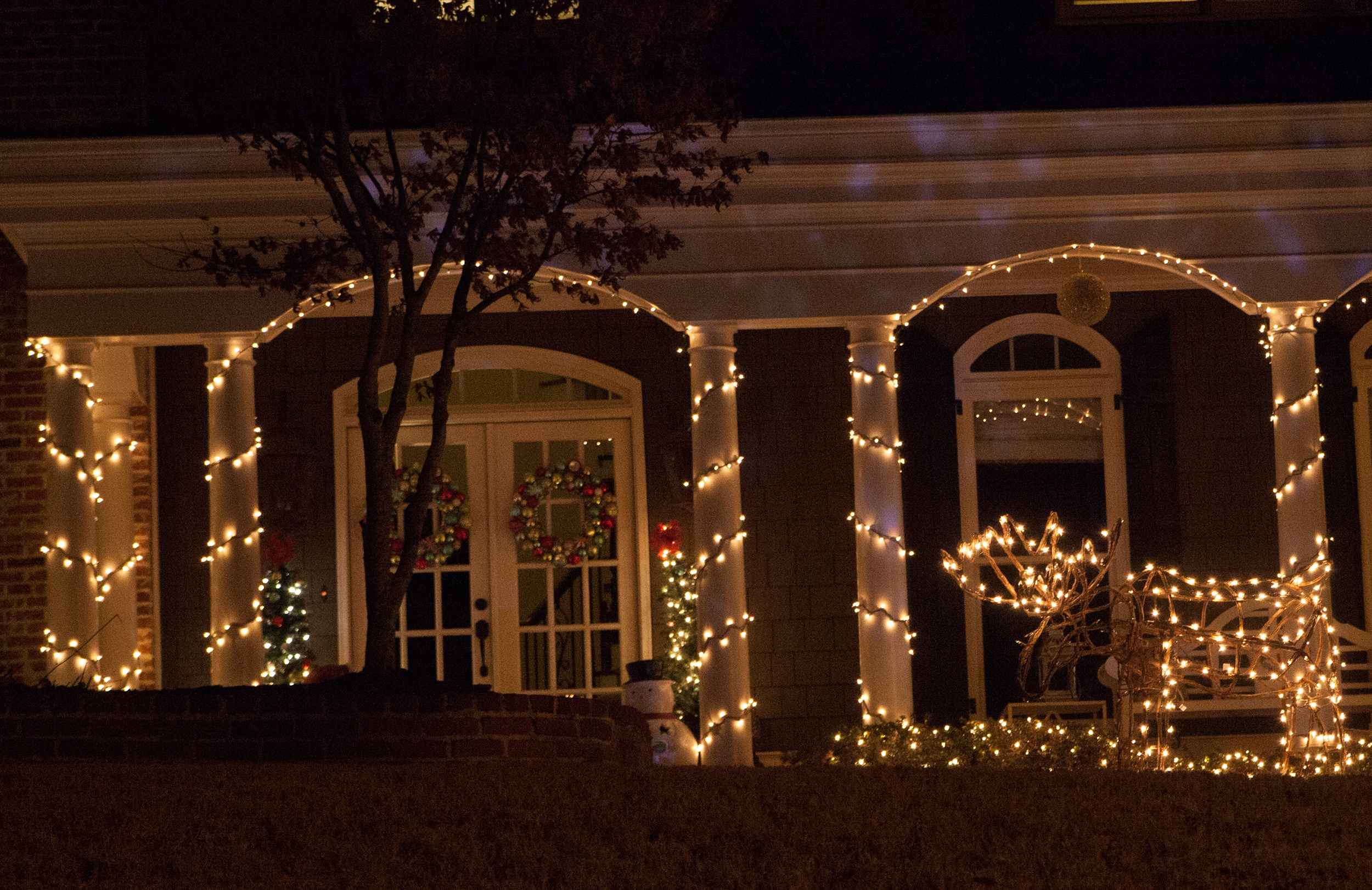 Porch columns wrapped with white string lights