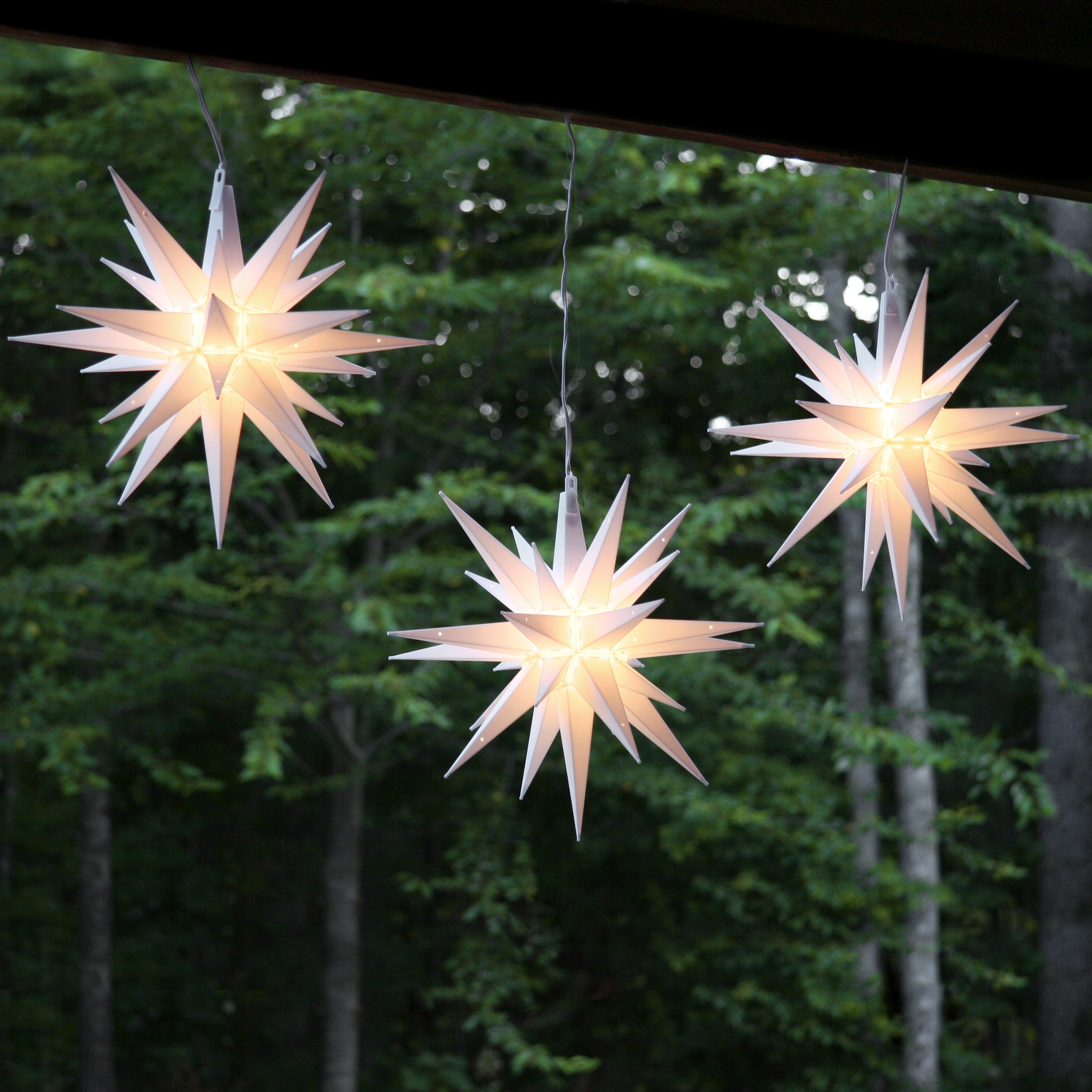 moravian stars hanging across the porch at christmas