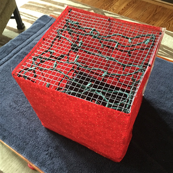 Wrapping fabric around chicken wire lighted gift boxes to use as outdoor Christmas decorations.