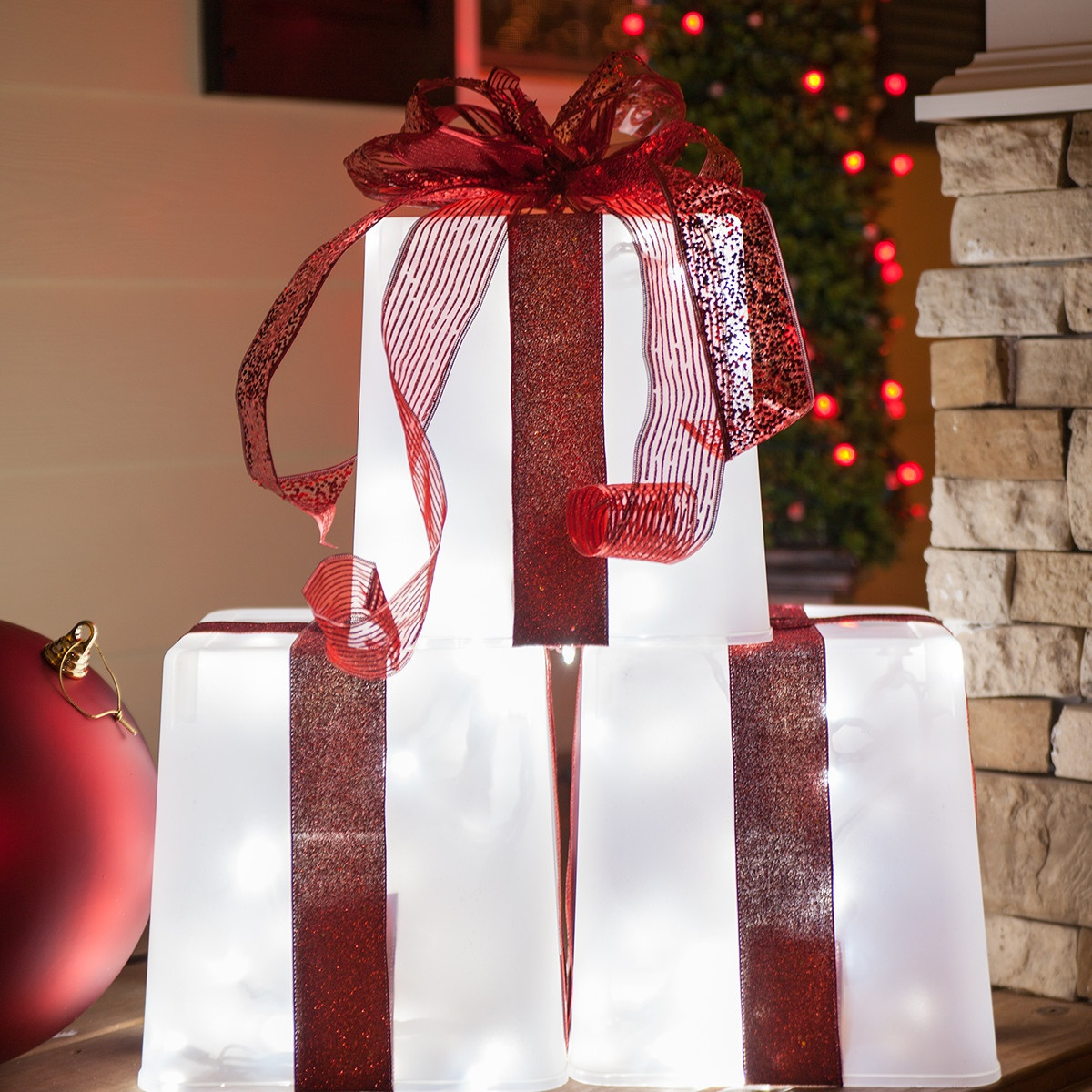 Create DIY lighted gift boxes using plastic containers, string lights and Christmas ribbon.