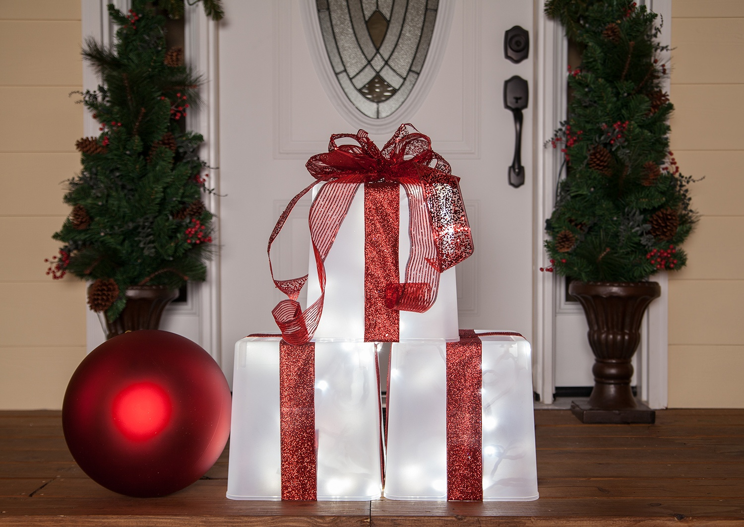 Easy DIY Christmas decoration - create a lighted gift box with a plastic container, ribbon and lights.