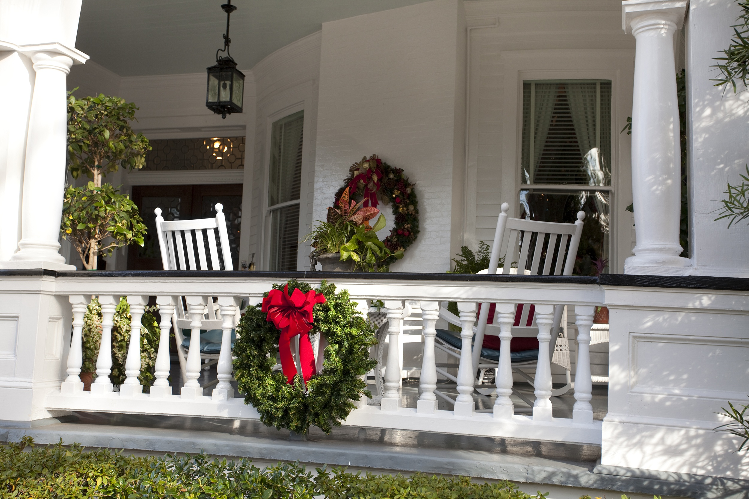 create a festive christmas porch with wreaths hanging along railings and down the staircase