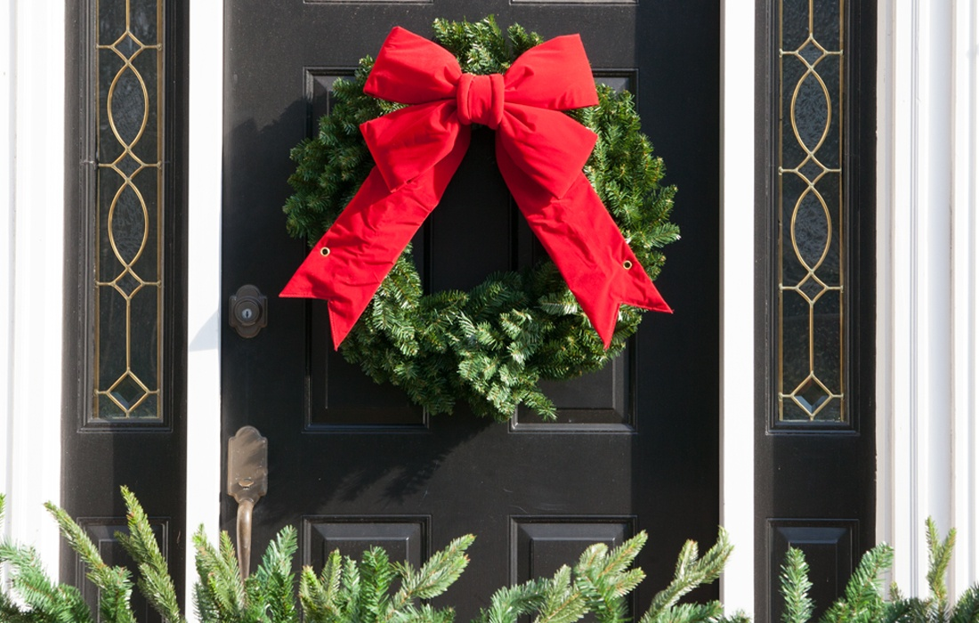 hang a christmas wreath on the front door adorned with a classic red bow