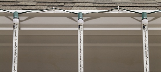 grand cascade led light tubes hang across the roof using gutters hooks