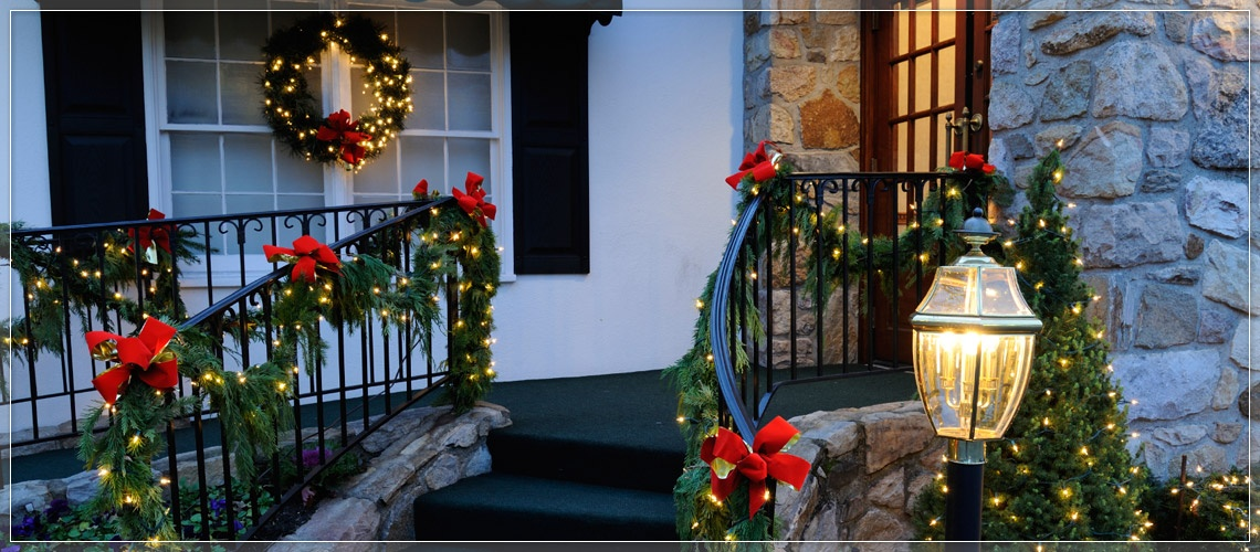 Stairway adorned with lighted garland and red Christmas bows