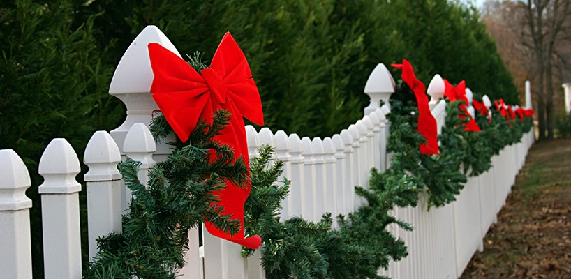 Christmas garland hanging across a front yard fence.
