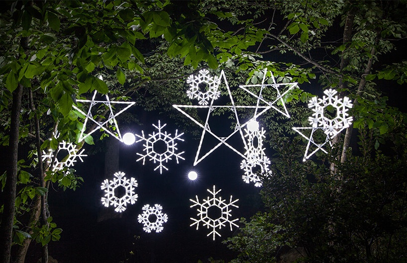 Lighted Christmas Snowflakes And Stars Hanging From Tree Branches.