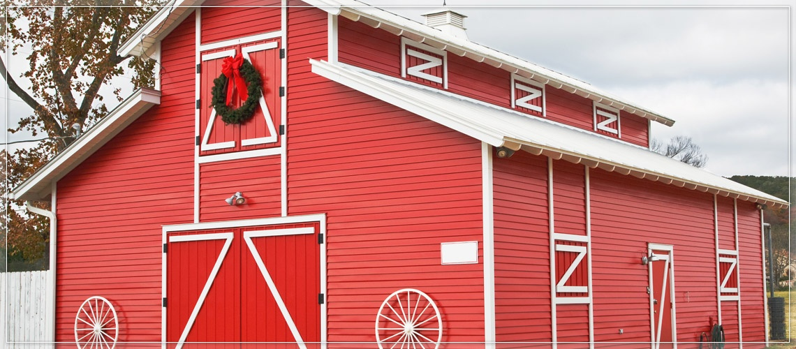 Red barn decorated with Christmas wreaths