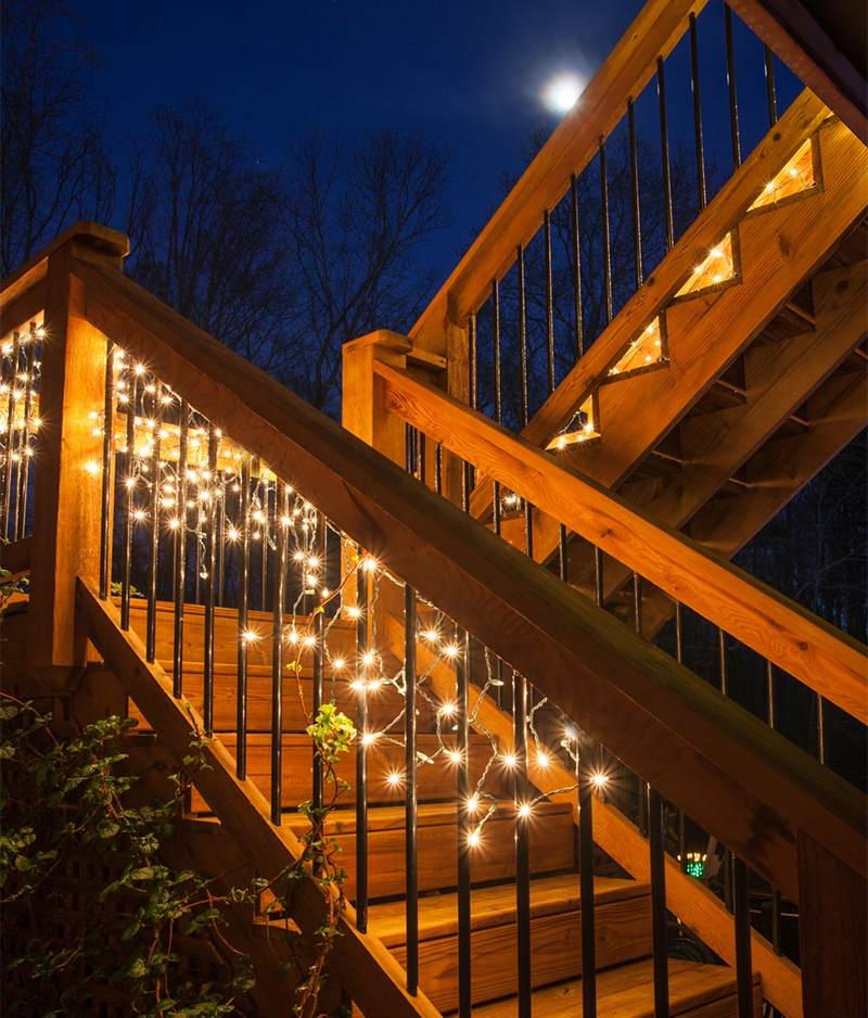 Hang Icicle String Lights Across Deck Railings to Illuminate a Backyard Party.