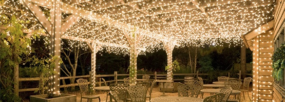 Icicle Lights Hanging Above a Covered Patio Dining Space