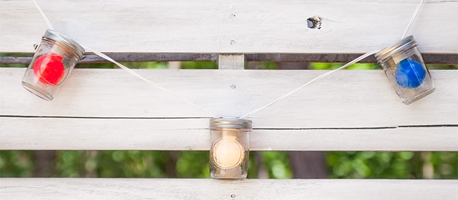 Globe Lights Inside Mason Jars Hanging on A Fence