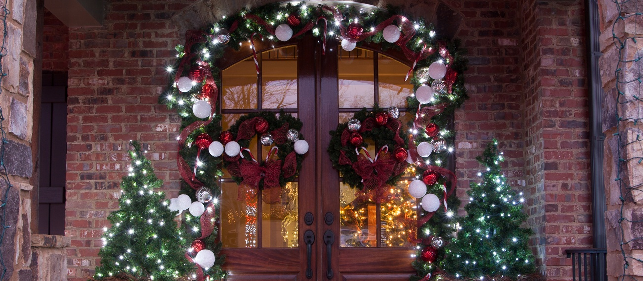 Decorate the front door with Christmas greenery and ornaments.