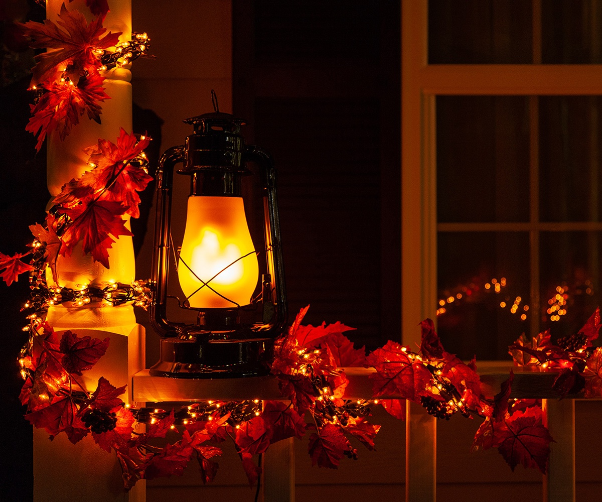 Garland Lights & Fall Leaf Decorations Wrapped Around a Porch Railing